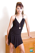 Leaning against wooden cabinet wearing black dress