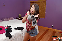 Drea Diamond standing beside bed in shorts