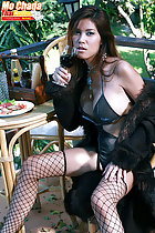 Seated at table drinking wine wearing lingerie in fishnet stockings