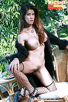 Mo Chada kneeling on chair long coat falling from her shoulders long hair dangling between her big tits legs parted exposing her pussy hand on fishnet stockings