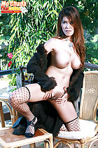 Kneeling on chair and bench spreading her pussy long hair falling over her big tits wearing fishnet stockings and high heels