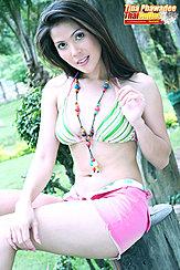 Sitting On Tree Stump Wearing Bikini Top In Shorts